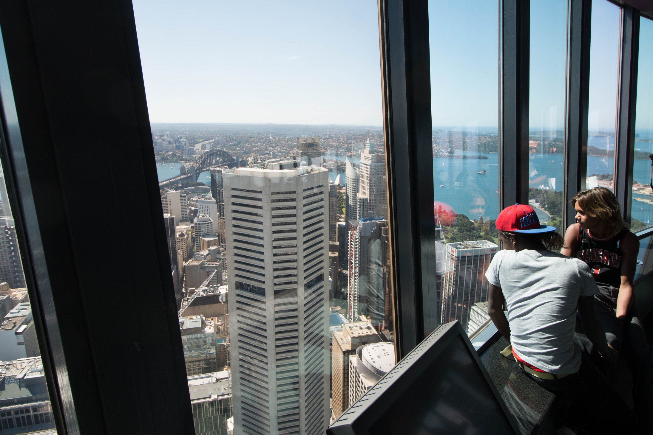 Lester Gumbula and Nehemiah Farrell inside Centre Point Tower, Sydney, looking out towards the Harbour Bridge (on left)