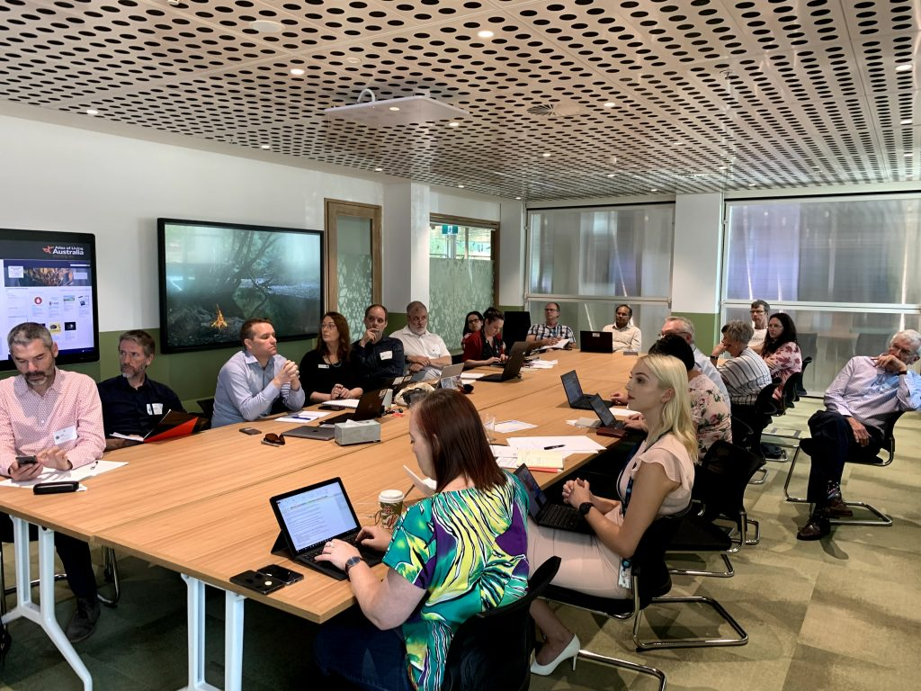 Participants of the Citizen Science Stakeholder Forum gathered around a large conference table with laptops open.