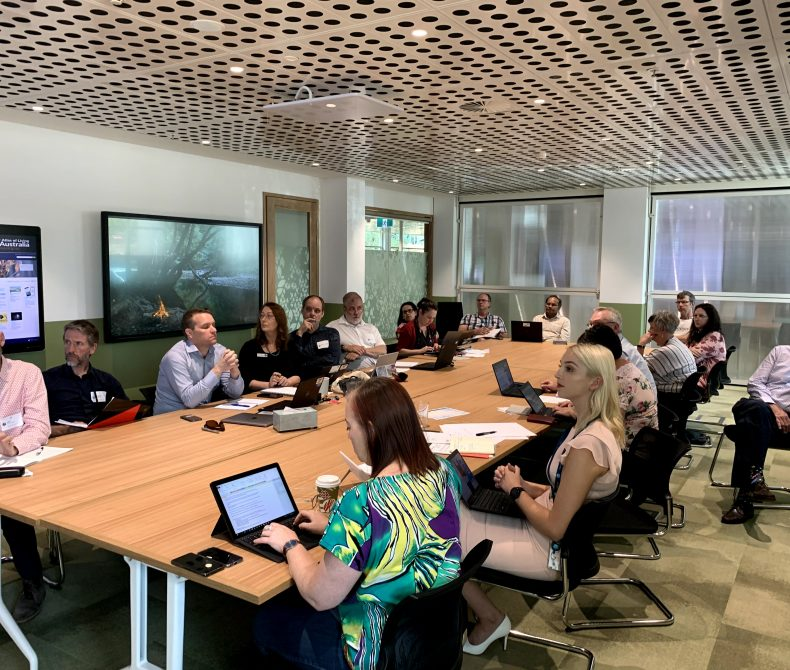 Bushfire Citizen Science Forum participants sitting around a table with laptops open